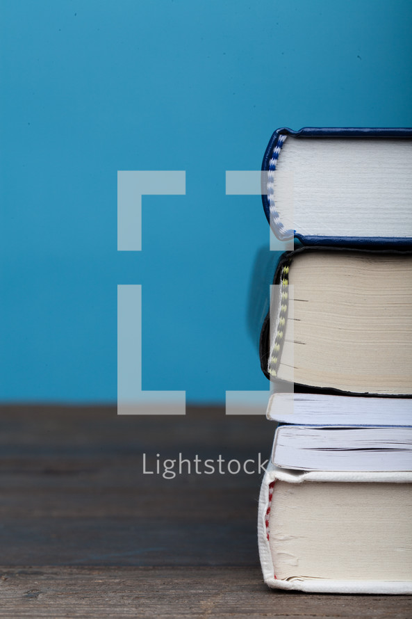 A stack of books on a wooden surface with a blue background.
