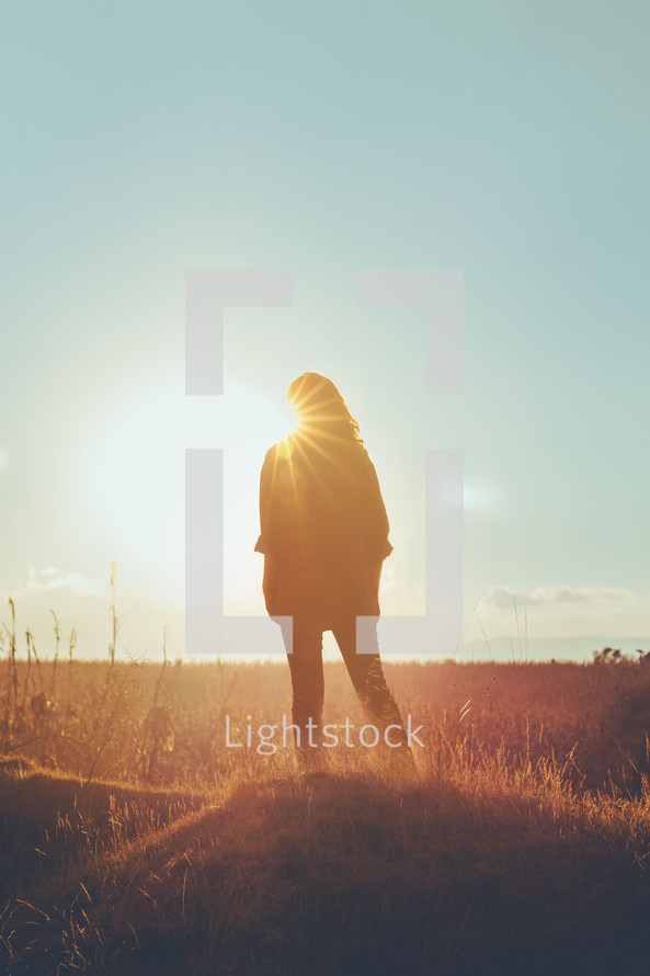 silhouette of a woman with a sunburst