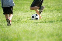 legs of young boys playing soccer