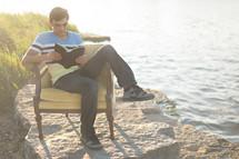 man reading the Santa Biblica in a chair on a beach