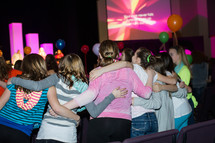 Girls in a church service with arms around each other.