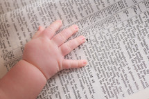 Close-up of infants hand laying on a bible opened to Psalm 46
