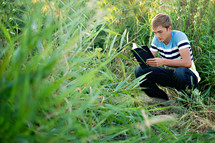 man reading the Santa Biblica in the wilderness