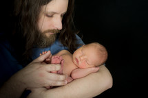 father with long hair holding his newborn baby