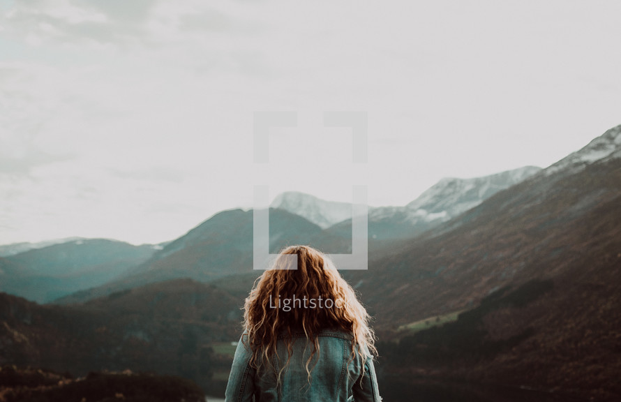 a woman looking out at the view of mountains
