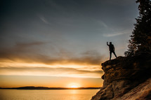 a person standing with a raised fist at the edge of a cliff at sunset