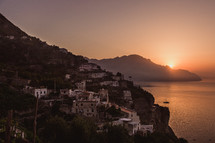 a village along a shoreline in Italy at sunset