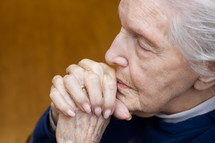 elderly woman with praying hands