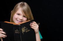 A little girl reading a Bible