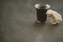 communion wine in a cup and bread on polygon background