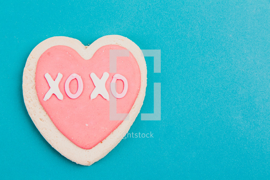 A pink and white Valentine candy heart on an aqua background.