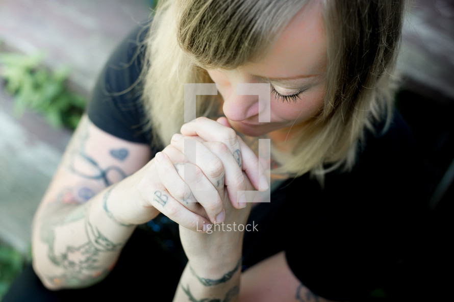 woman with tattooed hands praying