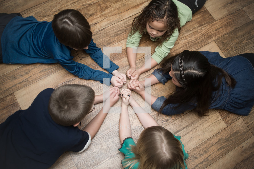 children with praying hands lying on the floor in a circle