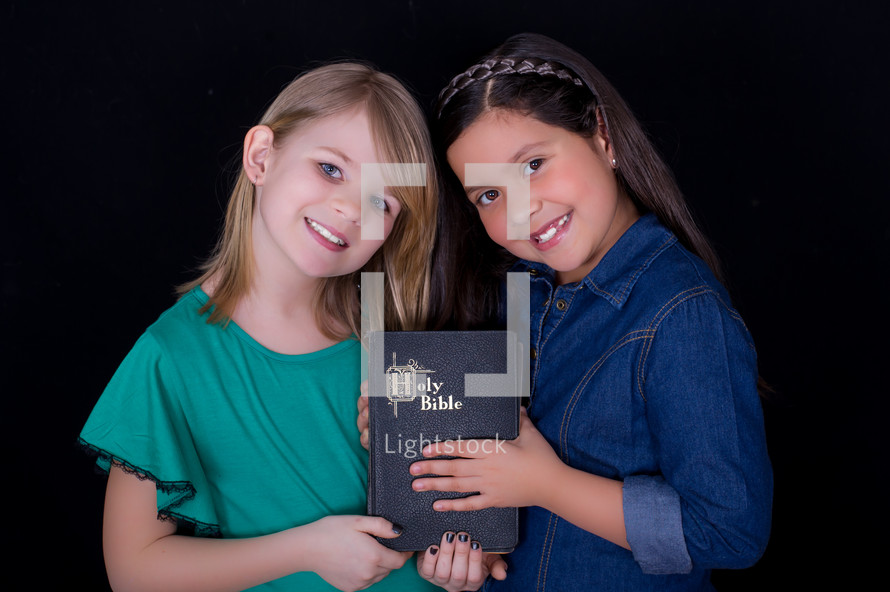Little girls holding a Bible