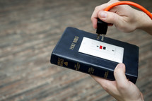 power of scripture - Bible with an outlet and power cord about to be plugged in
