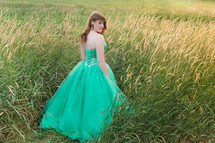 teen in a green prom dress in a field