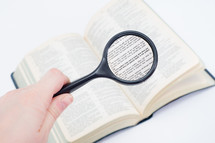 Hand holding a magnifying glass on a page of the Bible open to 1 Corinthians.