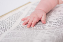 Baby's hand laying on an open bible