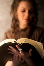 woman reading a Bible and a rosary bookmark