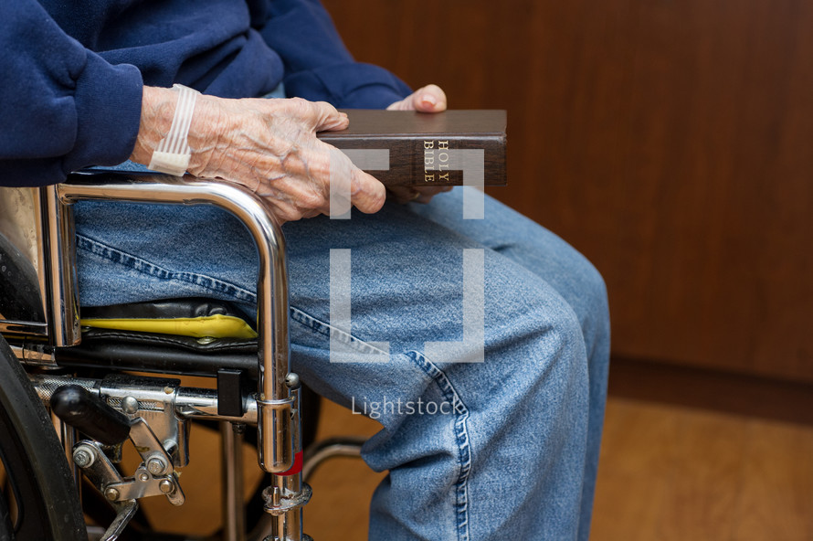elderly woman holding a Bible
