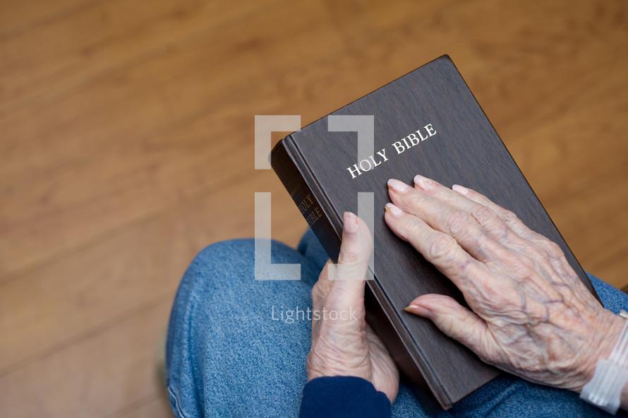 elderly woman holding a Bible