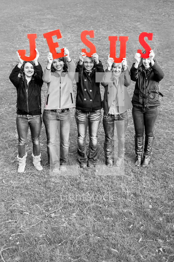 Teens holding up the word JESUS