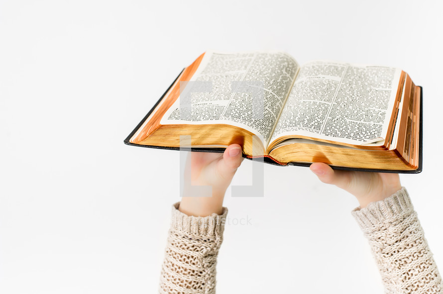 A girl holding an open Bible up in the air