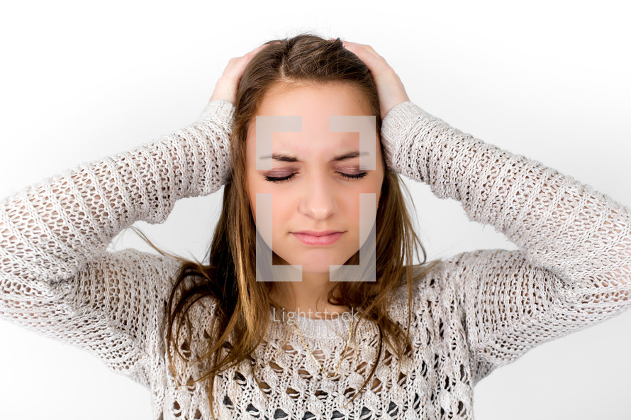 Girl with her eyes closed, frowning, holding her head as if it hurts.