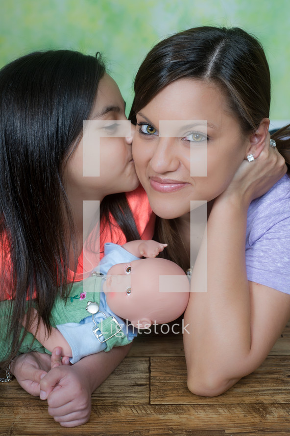 little girl kissing mother on the cheek