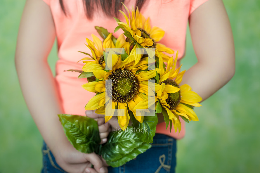little girl holding sunflowers behind his back