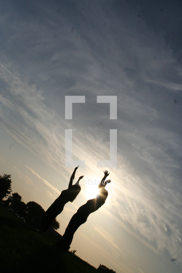 two women with their arms raised to the sky