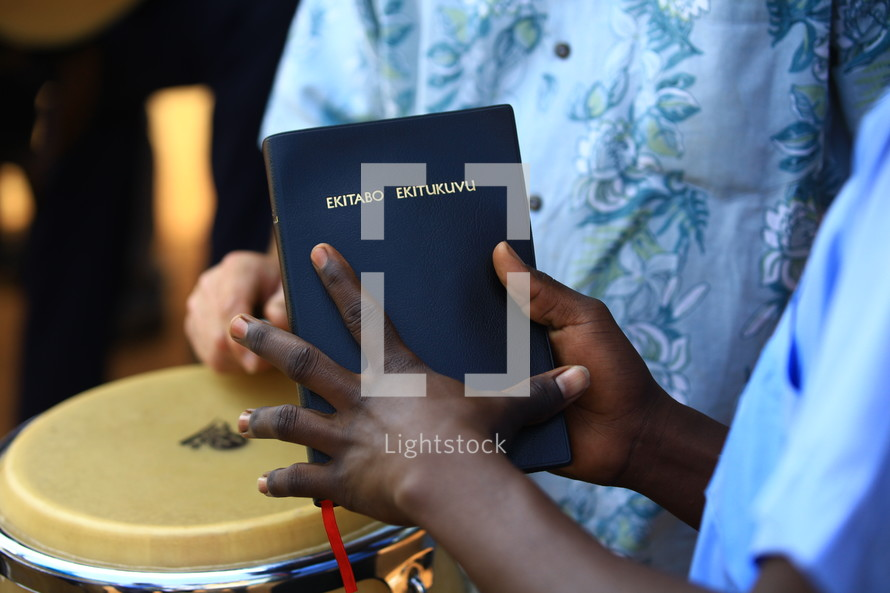 Hands holding Bible with musician in background.
