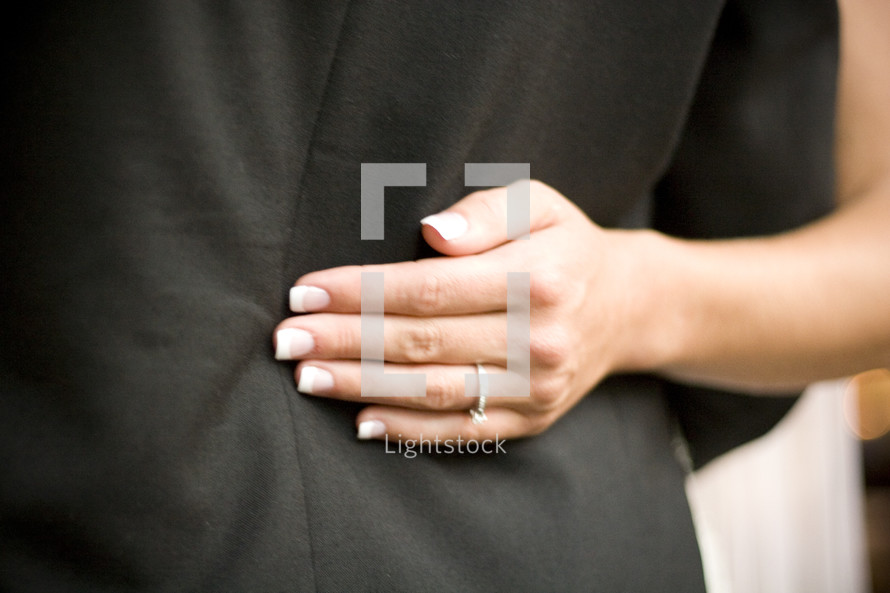 Woman's hand resting on back of man's jacket.