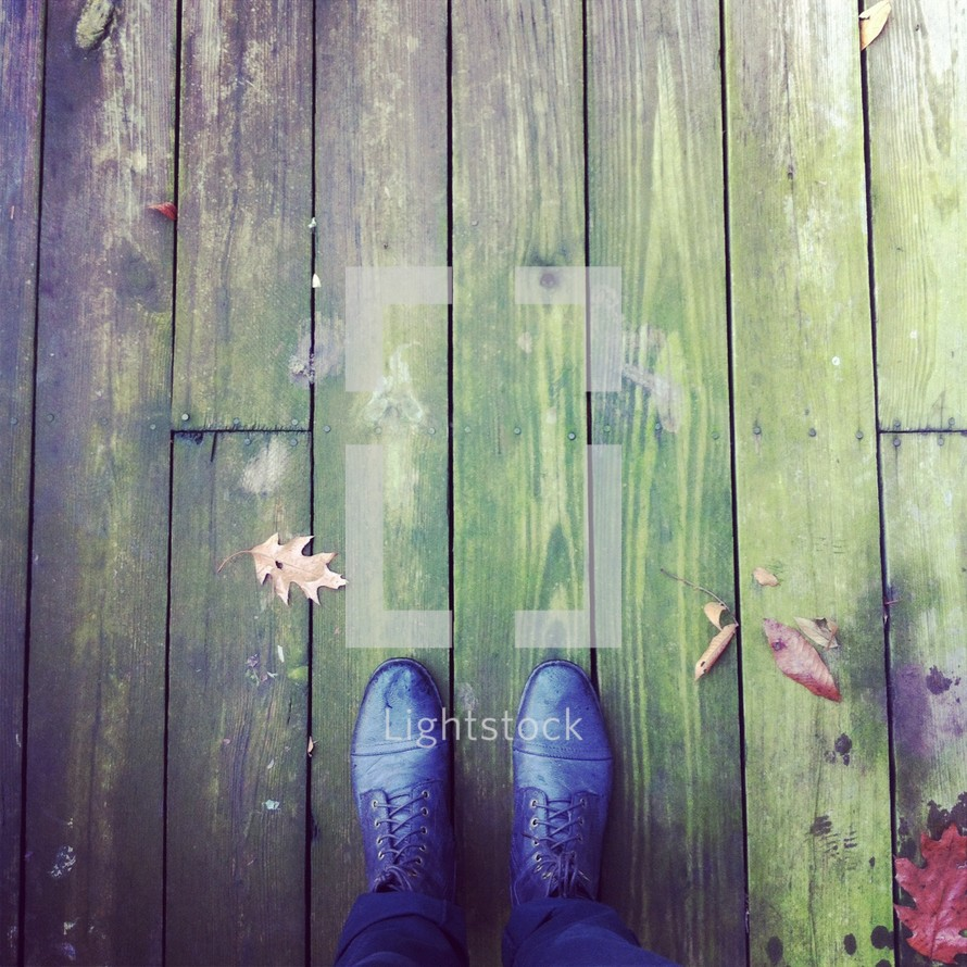 leaf and shoes on a a wood deck