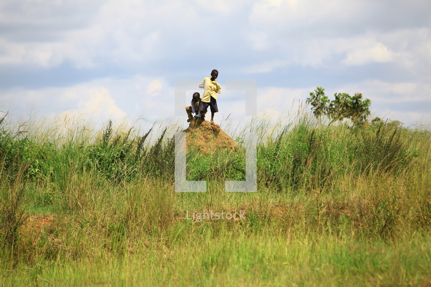 African boys on dirt mound