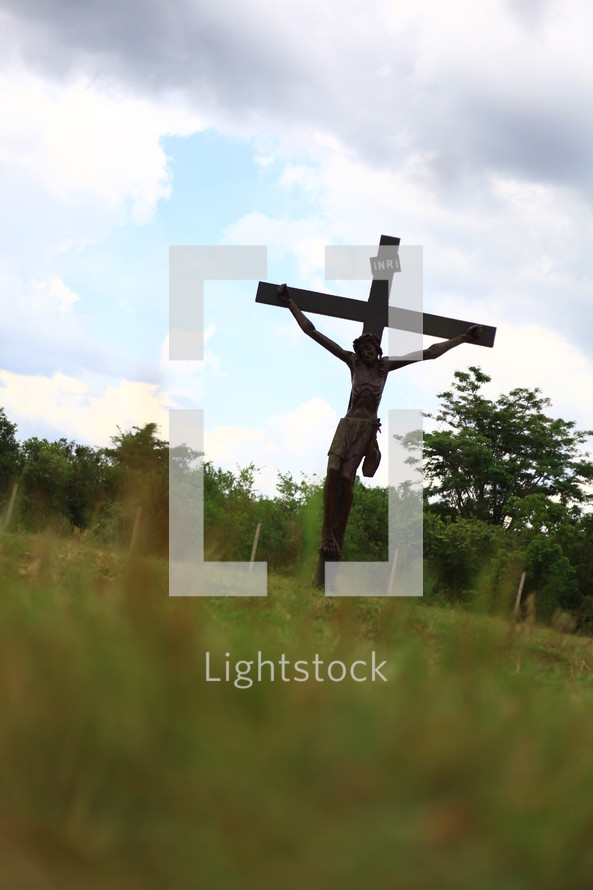 sculpture of the crucifixion of Jesus in a field