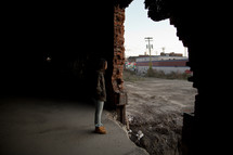 a person standing in front of a hole in an abandoned building