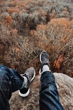 feet hanging off the side of a mountain over fall trees in a forest