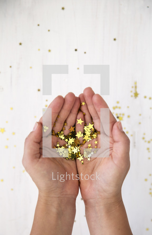 cupped hands holding star confetti