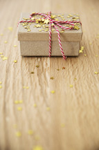 star confetti and red and white string around a brown paper gift box