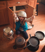 a child playing with pots and pans
