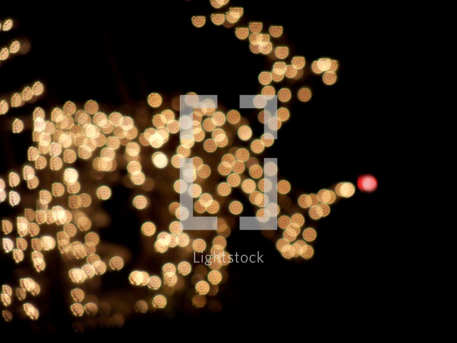 A dazzling array of white Christmas lights appear in the background lighting up the night sky  in the shape of a reindeer with decorative Christmas light bulbs that bring a warmth to the night air.