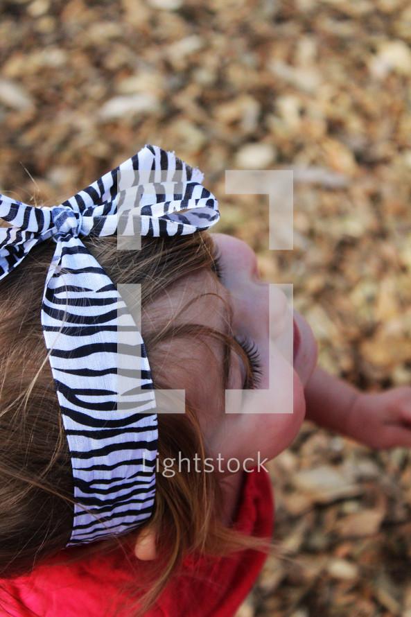 Smiling toddler girl walking through leaves.