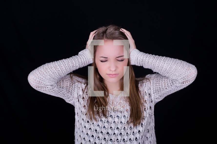 Girl with eyes closed, frowning, holding her head with her hands.