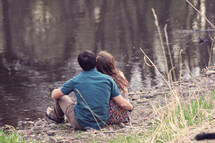 a couple sitting at the edge of a pond