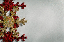 red and gold Christmas snowflake ornaments on a white background