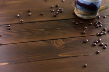 Coffee beans and a coffee cup on a wooden surface.