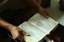 man reading an open Bible on a coffee table in front of a couch