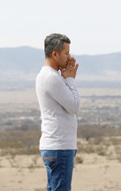 a man in prayer with a desert mountain view