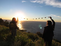 a couple holding a string of paper hearts in the air near the ocean
